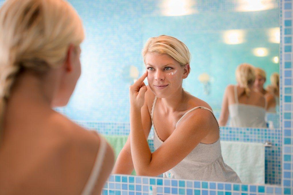 woman applying moisturizer around her eyes