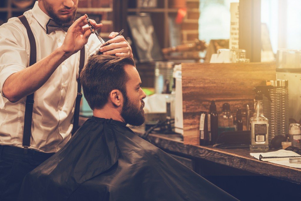 man getting a haircut in a barbershop
