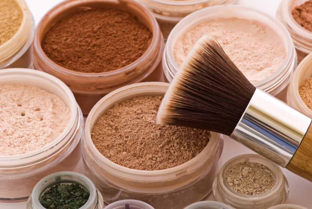 different colors of face powders and a brush