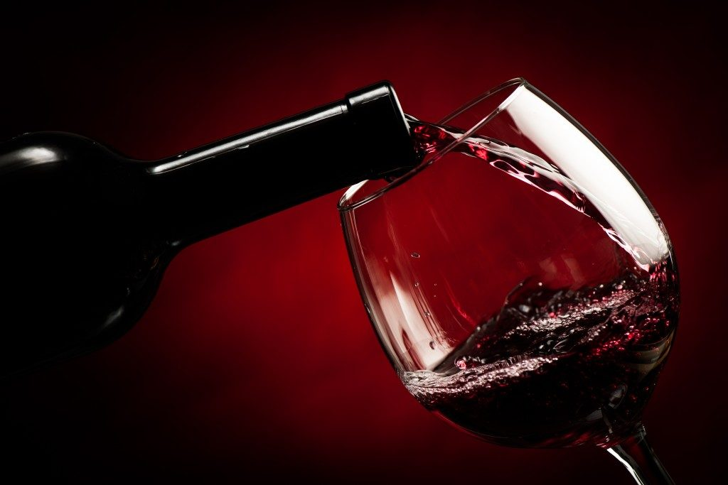 close up of red wine being poured in a wine glass